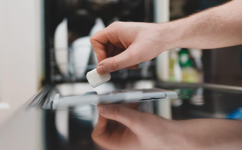 Man putting detergent tablet into dishwasher.
