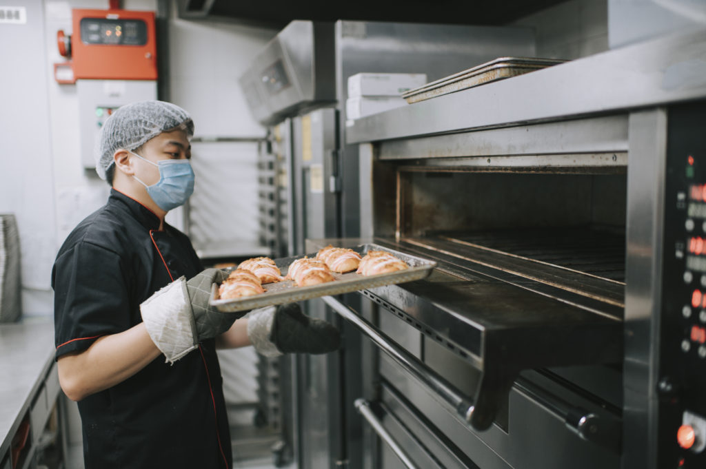 commercial kitchen bakery owner baking bread taking out from oven