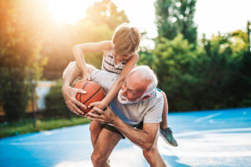 Grandfather and his grandson playing basketball.
